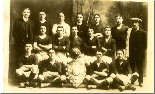 Lubel is seated to the left of the shield